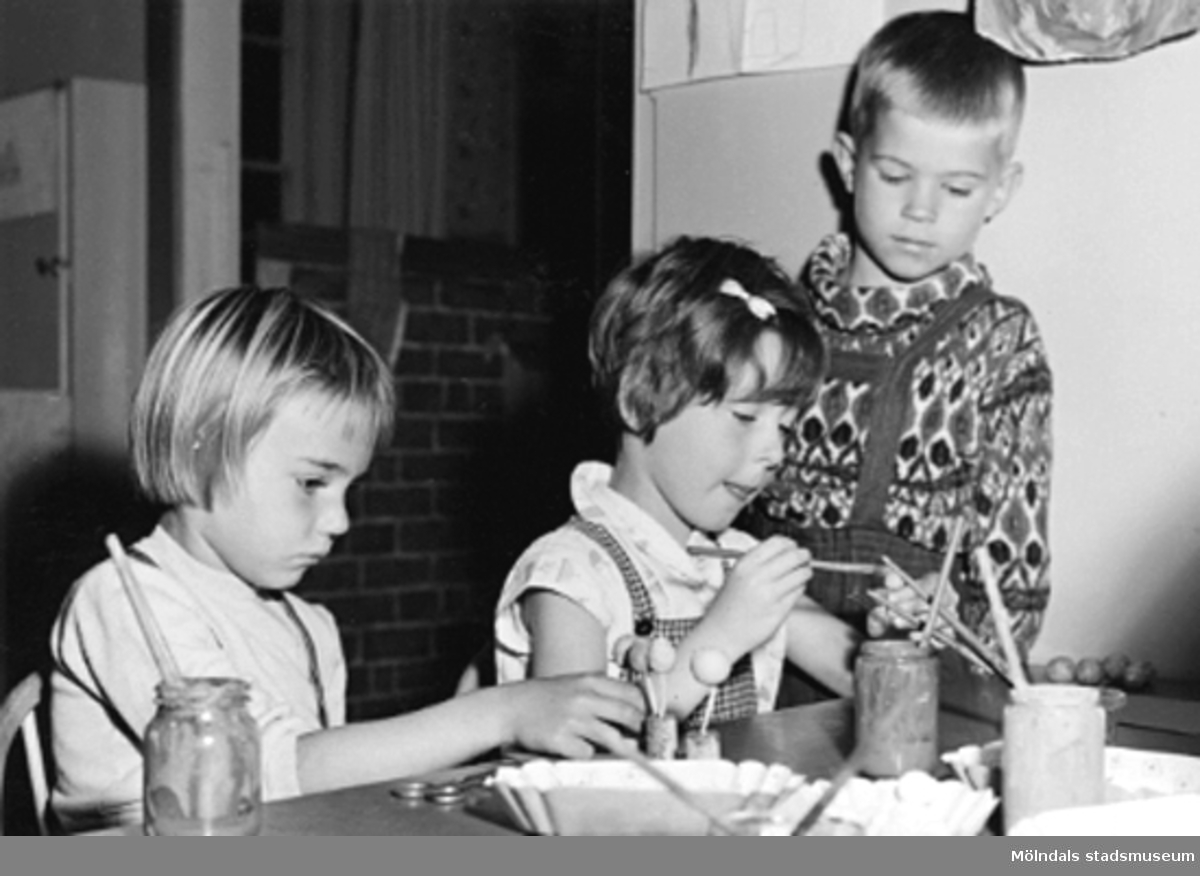 Tre barn som pysslar vid ett bord. Holtermanska daghemmet 1953.