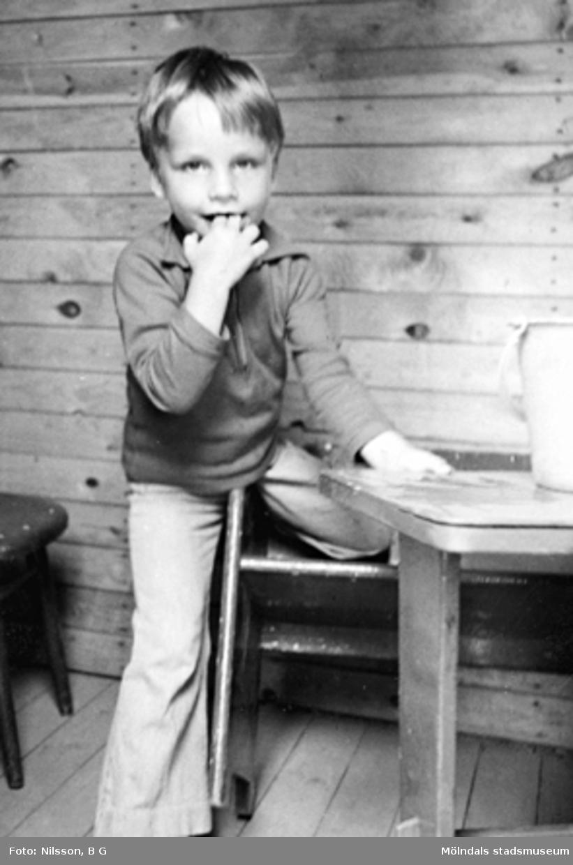 En pojke inne i ett förrådshus. Holtermanska daghemmet 1973.