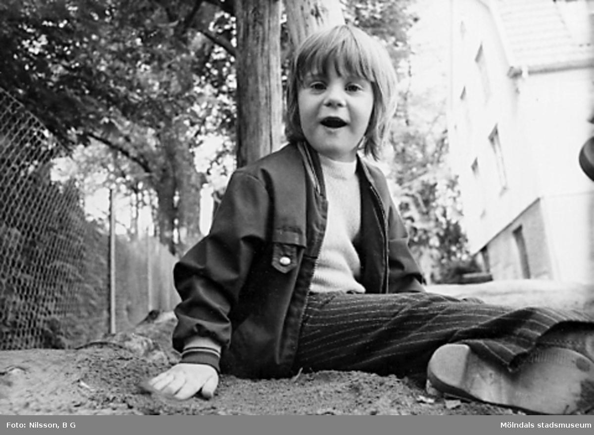 Ett barn sitter i sandlådan. Holtermanska daghemmet juni 1974.