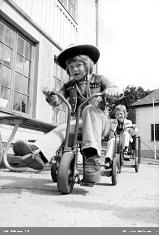 Två pojkar som cyklar på trehjulingar varav den främre är klädd i cowboy-kläder. Holtermanska daghemmet juni 1974.