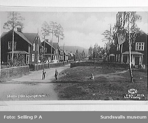 Väg kantad av arbetarbostäder i Ljungaverk. På vägen står ett par pojkar, varav en med en leksak i form av ett tunnband.