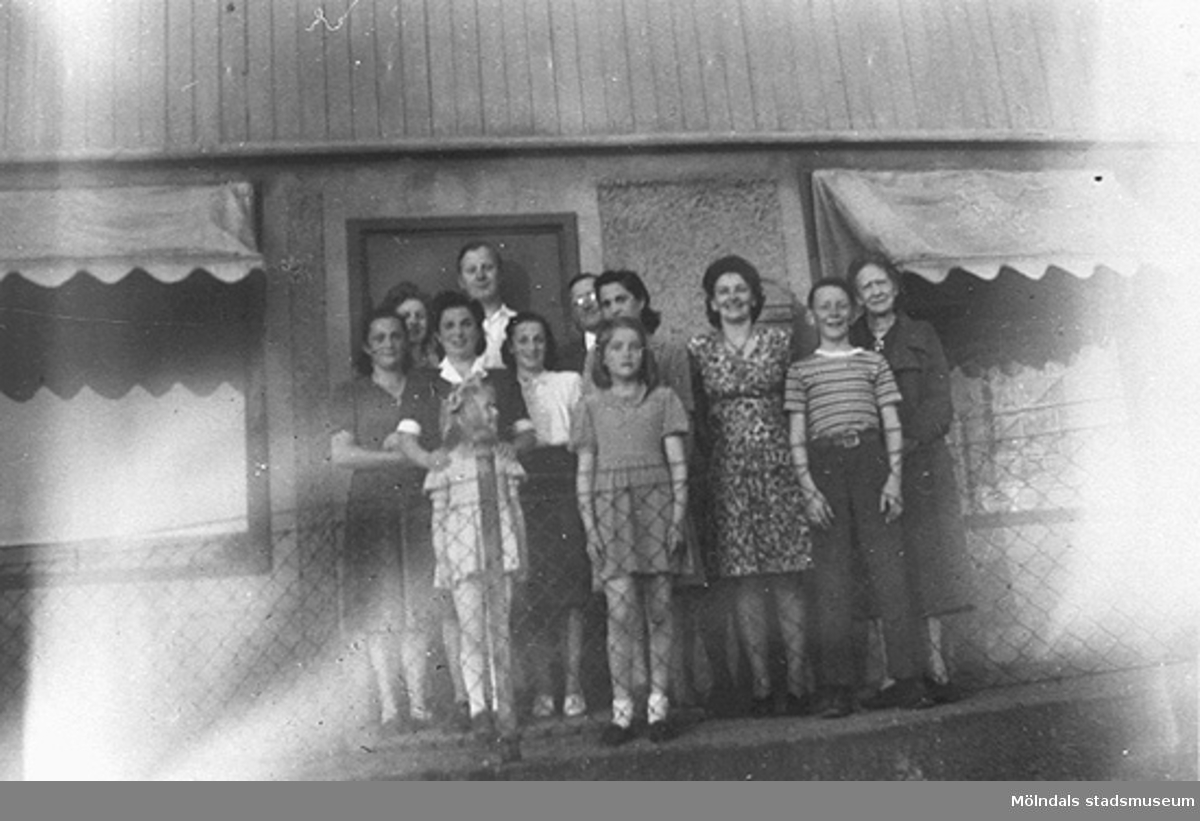 """Längst fram står systrarna Ulla-Britt och Marie-Louise Johansson. Andra raden från vänster: Mina, Rosa, Madzia (tre systrar), Sara (kusin) och Ragnhild Johansson (mor till U-B och M-L). Längst bak står Gustav Johansson (pappa till U-B och M-L). Längst till höger står Aina Håkansson.""""Våra flickor"""" som familjen Johansson kallade de tre polska judiska systrarna och deras kusin (Rosa, Mina, Madzia och Sara) som kommit från ett koncentrationsläger till Mölndal 1945, fick bo i källaren hos familjen Johansson och använda en del av trädgården. De tyckte att den var ett paradis. De flyttade till Israel 1948."""