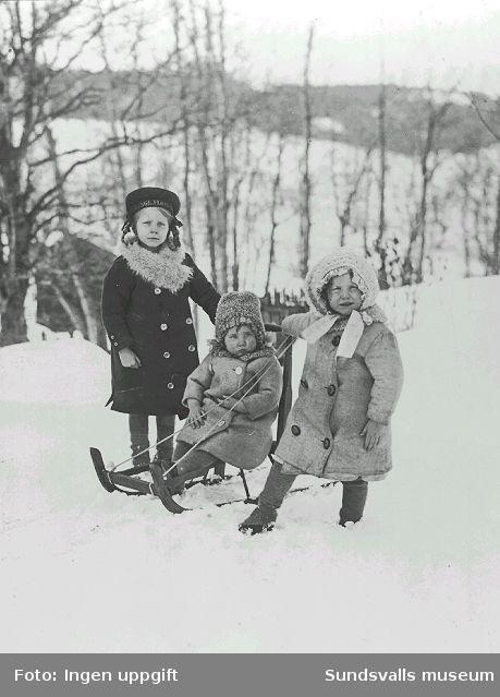 Vera, Maiken och Ingagreta Håkansson vid bykhuset vid Sidsjöbäcken, Sallyhills gård. Vera har sina nya sjömansmössa på sig. Sallyhills gård var flickornas barndomshem.