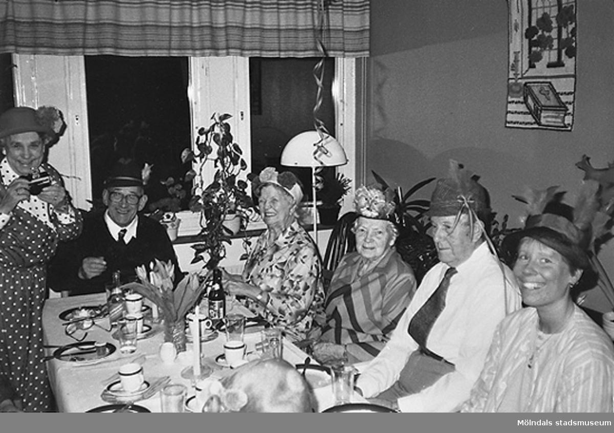 Flera glada personer, iklädda hattar, sitter vid ett bord. Okänt årtal.