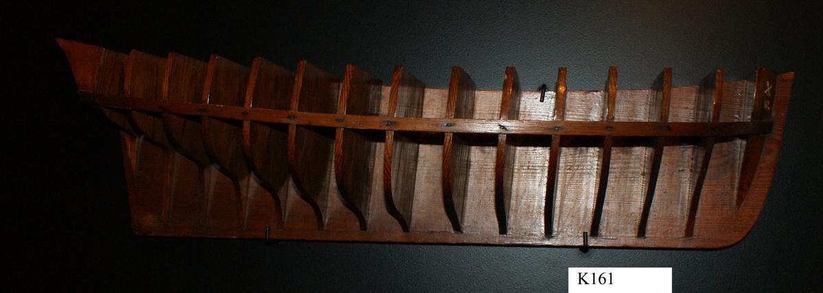 Gavelmodell å fartyg byggt på örlogsvarvet i Karlskrona. Halvmodell av ett mindre segelfartyg troligen från 1700-talet, med akterspegel, utan galjon och utmärkning av däck, men med uppbyggd stäv och köl. Modellens för- och akter utförda av massivt trä och däremellan är fastsatt 13 träskivor, gavlar, som utmärker skrovformen. Gavlarna är fixerade av en ribba. För, akter och gavlar fastsatta på en träplatta. Allt fernissat.