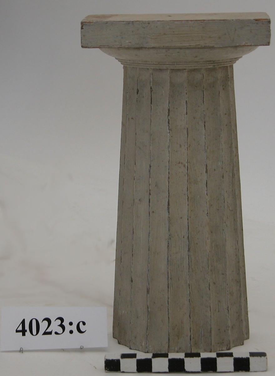 """Pelare, eller kolonner, släta och räfflade (7 st halvkolonner, räfflade). 20 st. modeller av trä, avsedda som fasadprydnader. Pelarna är räfflade med halvcirkelformig basyta. De är vitmålade. Kapitälen är av närmast dorisk stil. Pelarna utgör modeller till gavelkonstruktion för nya inventariekammaren på varvet 1785-87. De sammanhängs troligen med en serie av gavelmodeller och pelare, som finns i kistan i sal 1 och vid norra delen av väggen i samma sal. (K 2244)  Halvkolonn, kannelerad med kapitäl och fast abakus. Målad i gråvitt. Tidigare märkt: """"4"""". Vid inventering 1998 fanns det 2 stycken 4023:c.  Bas B = 90mm  Abakus L = 120mm"""
