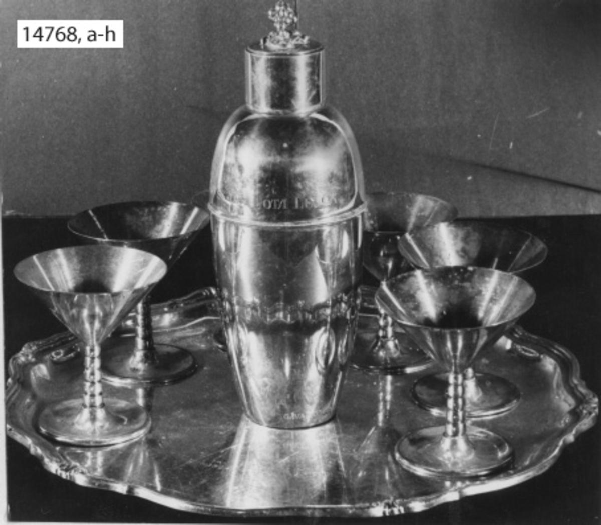 Servis, cocktail-, av silver. Tumlare. Ingravering: H.M. KRYSSAREN GÖTA LEJON. (Skänkt till kajutan).