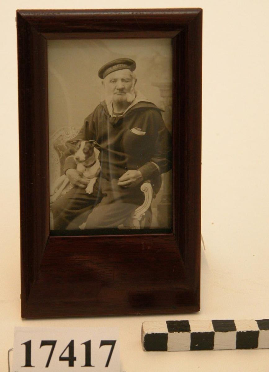 """Fotografi inom glas och ram visande äldre sjöman iklädd yllebussarong och byxor samt skjorta, rundmössa  med mössband """"Kongl. Flottan"""".  Mannen sitter i en snidad, vitmålad stol och har en hund i knäet. Ramen av mahogny, med underkantens B= 37 mm, övriga kanter B= 13 mm. Glaset är konvext. Baksidan är av svart papp och försedd med stöd för placering på bord. Neg.nr 13133"""
