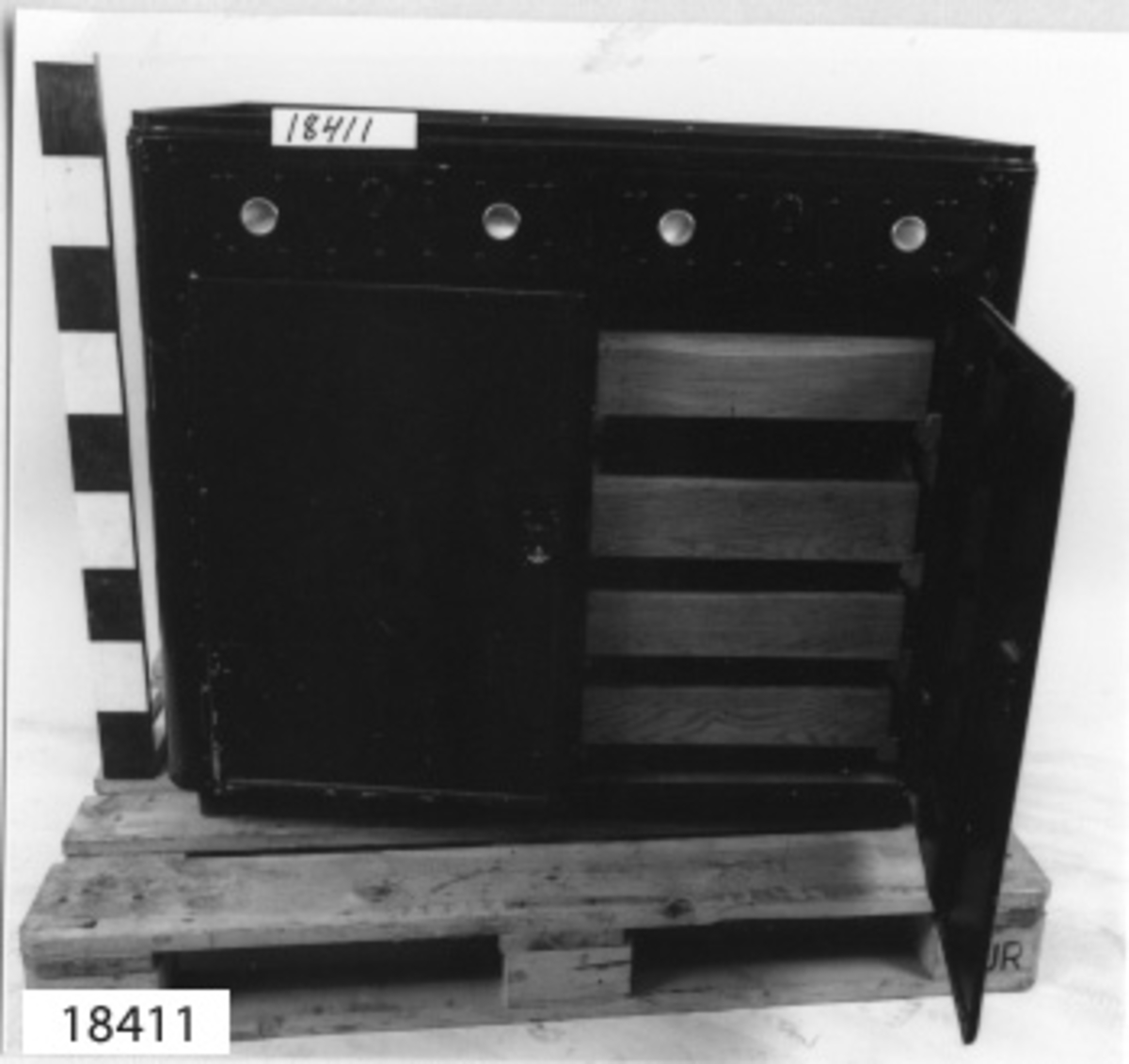 Mässkåp av lättmetall målad i mahognybrunt med rundade framkanter, på framsidan två lådor och två skåpsdörrar. Lådorna är placerade ovanför skåpsdörrarna. Samtliga låsbara, en nyckel tillhör. Ovala nyckelhål. Lådorna är försedda med nitar samt vardera två handtag i form av runda knoppar av koppar. Skåpsdörrarna har en list runt kanten. Ovansidan försedd med slingerkant av målat trä. Skåpet står på träsockel. Omålad baksida. Invädigt omålade lådor. Skåpen är försedda med hyllplan av plywood med runda hål för placering av dricksglas av olika storlekar, från 12 till 32 hål. Vänster skåp har tre hyllplan (ett saknas) och höger skåp har fyra hyllplan. Ingen märkning finns.