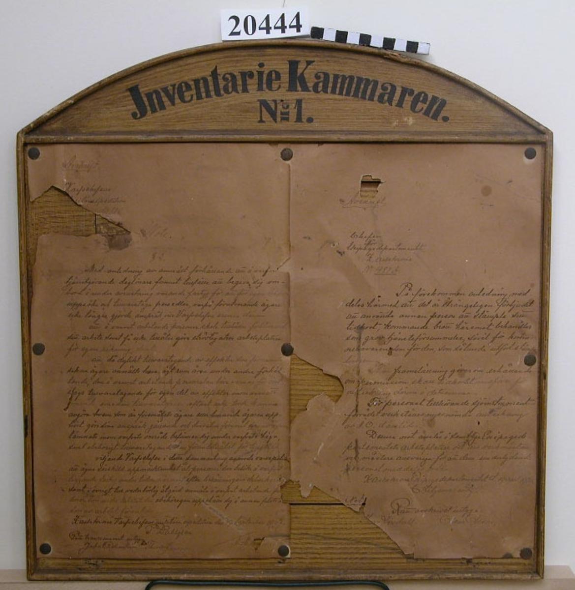 """Tavla av trä, rektangulärt format, ovankanten försedd med bågformat överstycke med text: """"Inventariekammaren No 1."""" Målad ekimitation på fram- och baksida. På framsidan sitter två papper fästade med häftstift, handskriven text; till vänster förbud mot all slags privat omhändertagande av föremål på varvets område, daterad 1907; till höger förbud att låta andra stämpla sitt tidkort, daterad 1920. Avskrifter finns som inventariebilaga."""