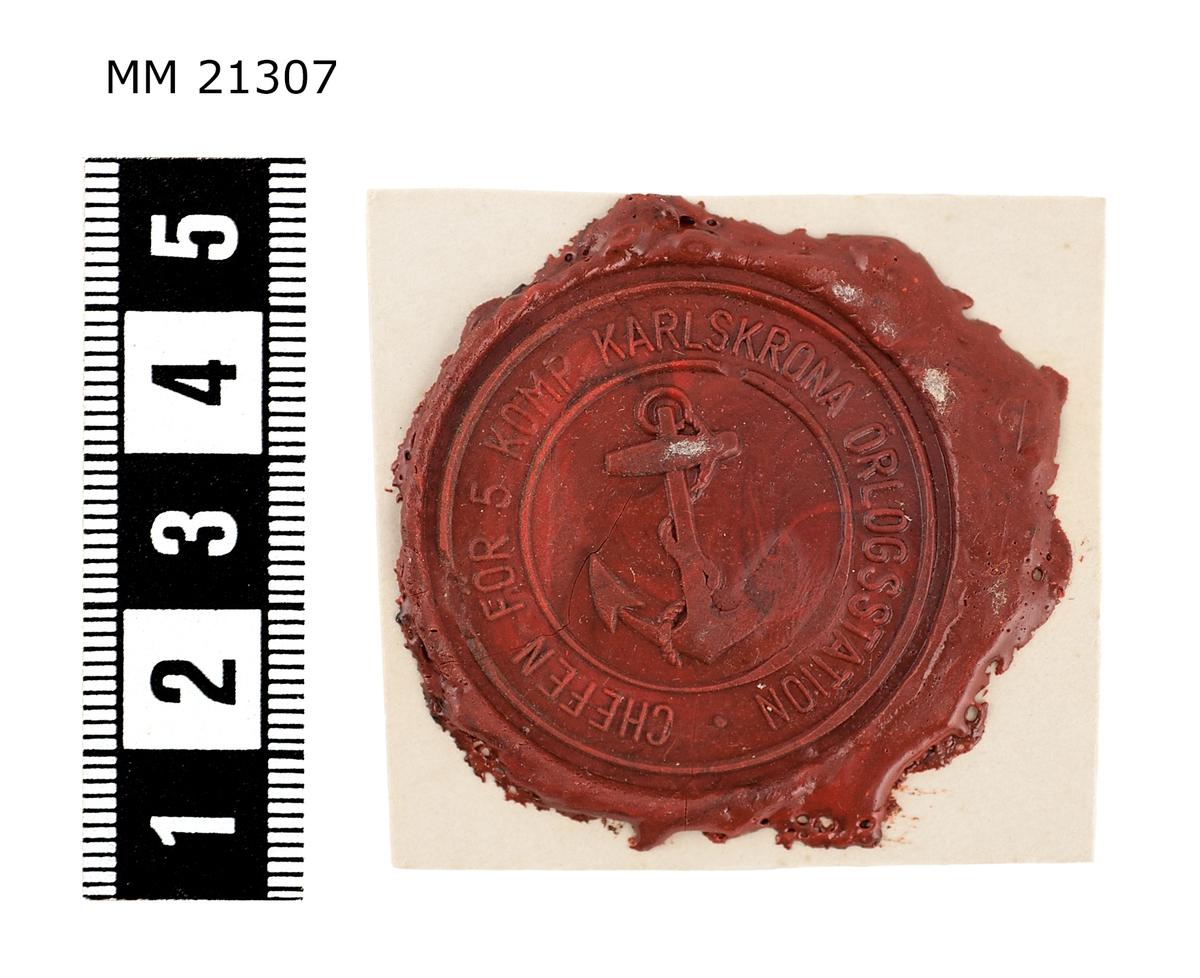 """Sigillavtryck av rött lack på papper. I mitten krönt sköld med tre kronor omgivet av serafimerkedja. Längs kanten text: """"Chefen för 5 komp. Karlskrona Örlogsstation""""."""