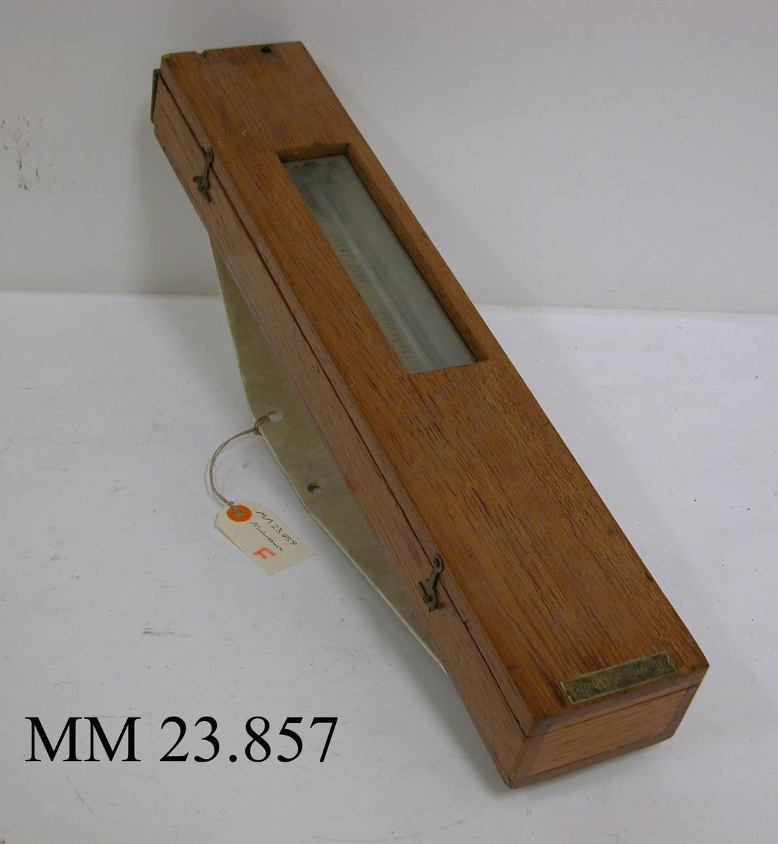 Långsmal rektangulär trälåda innehållandes en nivåmätare för ångtryck i pannrum ombord på jagare, kryssare etc. På trälådans framsida finns ett mindre glasfönster i storleken 205 mm x 50 mm, genom detta fönster går det sedan att avläsa den övre delen av mätstickan (övertrycket) inne i lådan. Vidare kan trälådan öppnas helt och blottar då hela nivåmätaren och dess mätsticka, såväl över- som undertryck, som går från + 30 CM till - 30 CM. Mätstickan är utförd i gul metall och är fastsatt i trälådan upptill och nedtill genom två handskruvar som gör stickan justerbar. Kring mätstickan löper ett glasrör som troligen fyllts med vatten från två mindre hål på trälådans ovansida. Längst ned på trälockets framsida sitter en liten metallplatta med texten: Aktiebolaget NORDISKA ARMATURFABRIKERNA Stockholm. På trälådans baksida sitter en metallstomme. Denna har troligtvis tillfogats vid ett senare tillfälle och hör inte ursprungligen till instrumentet. Möjligen har nivåmätaren flyttats mellan olika fartyg varefter olika uppsättningsanordningar varit av behov.