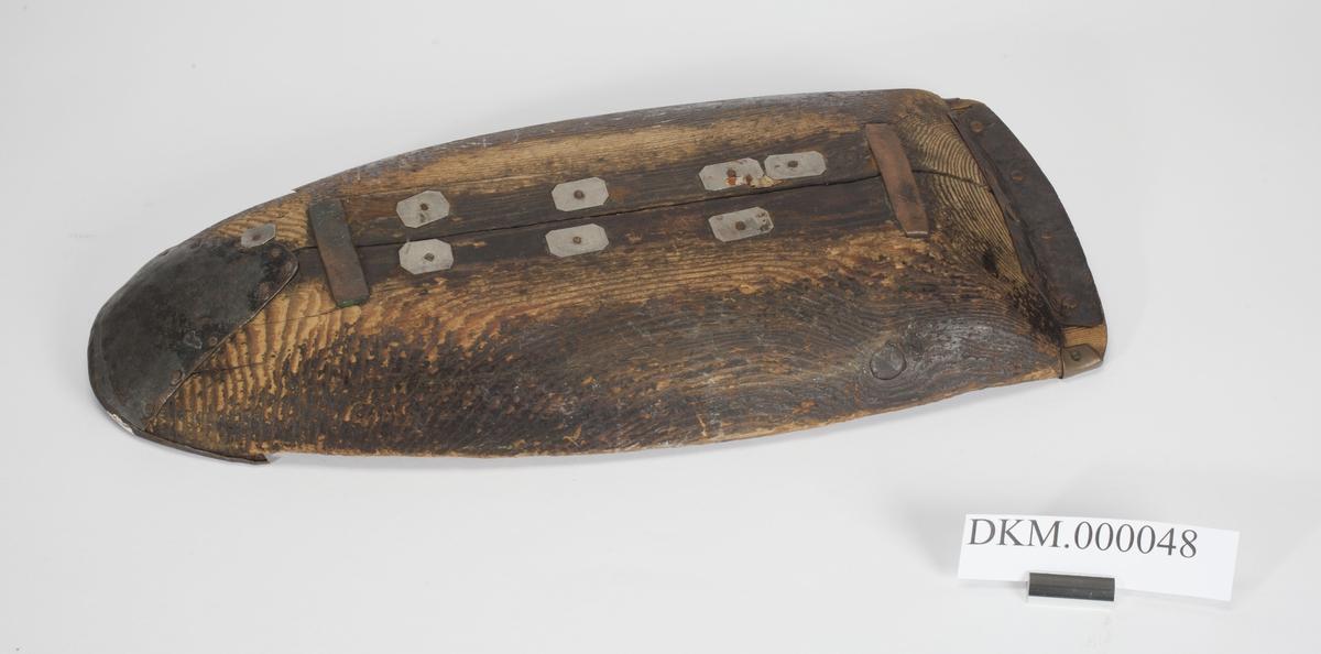 Avlangt trau med avrundet bunn som gjør at trauet minner om en åpen båt. Den ene enden er spiss, den andre enden bredere og svakt buet. Trauet har jernbeslag langs bunnen og i begge ender.