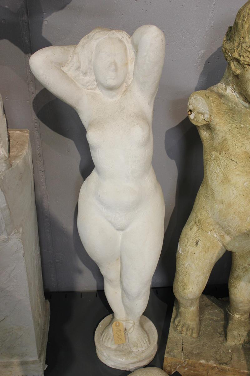 """Skulptur i gips av en naken kvinne med begge armene bak hode. I eldre protokoll er den kalt """"Rokokkopiken""""? så jeg går ut i fra at de har vært usikker på tittel. Se også nr.216"""