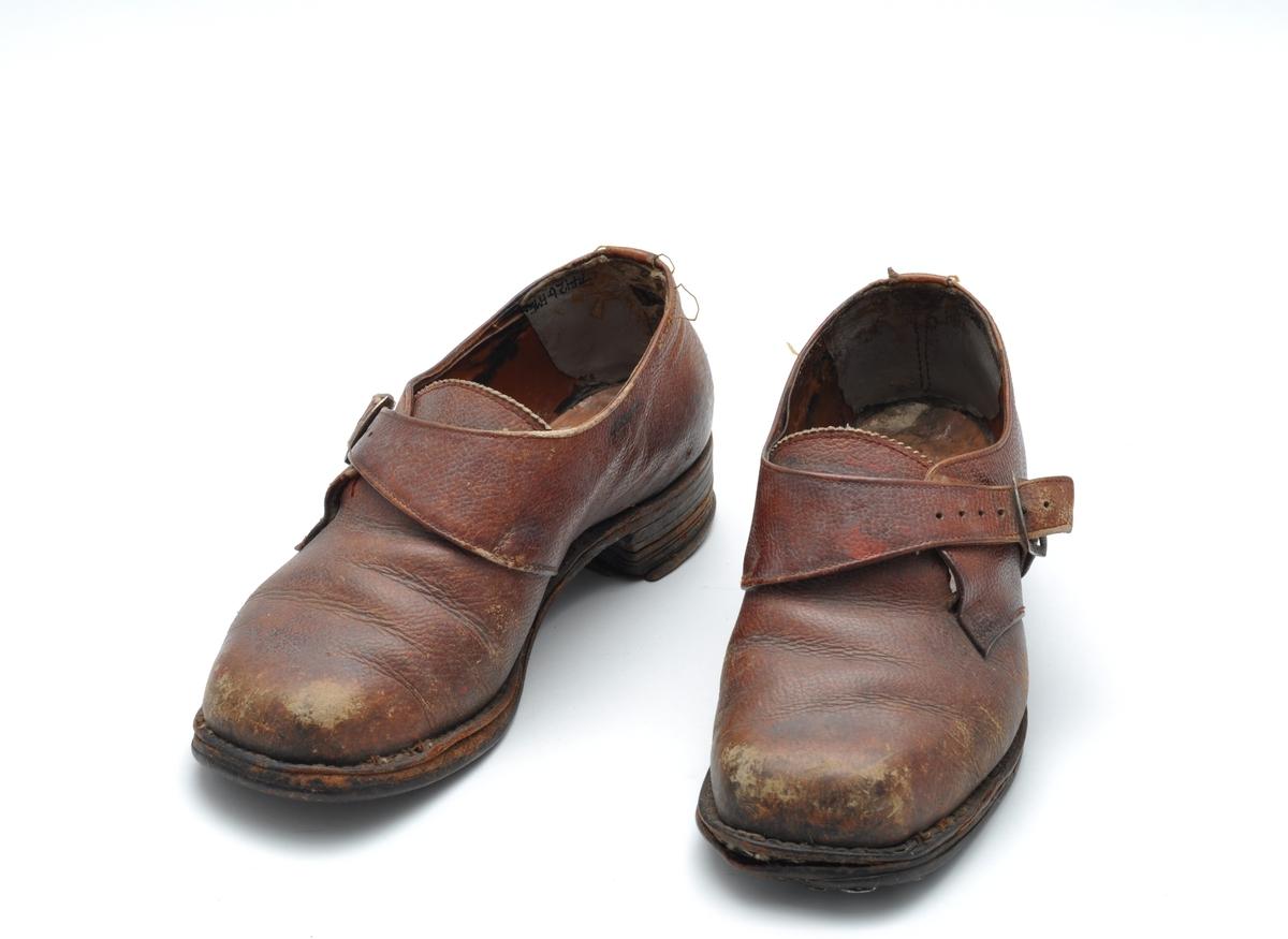 Kraftig damesko i brunt lær. Utesko, spasersko. Lav hæl, reim over pløsen. Skoene er velbrukt, har blitt forsterket med plugger (skospar) i sålen.