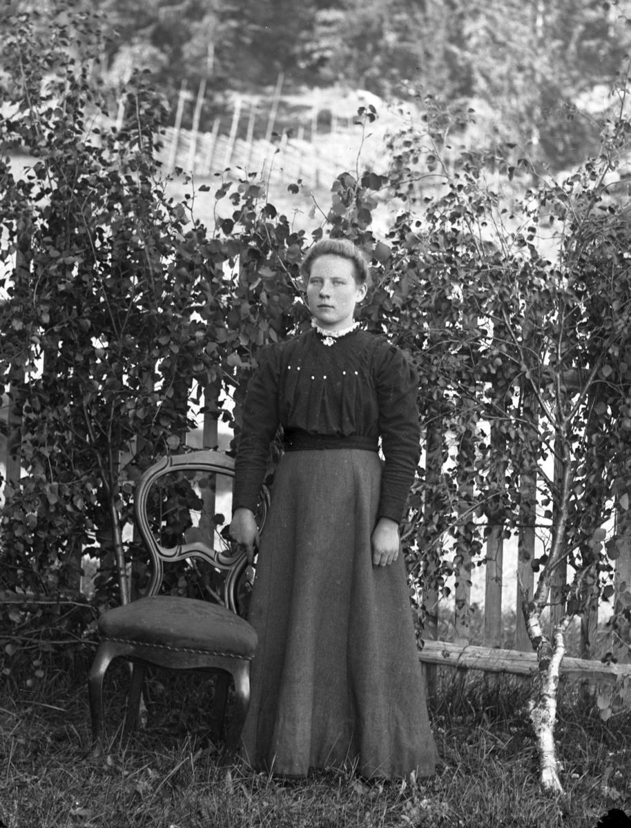 Kvinne i helfigur, ved stol, foran hvitt stakittgjerde