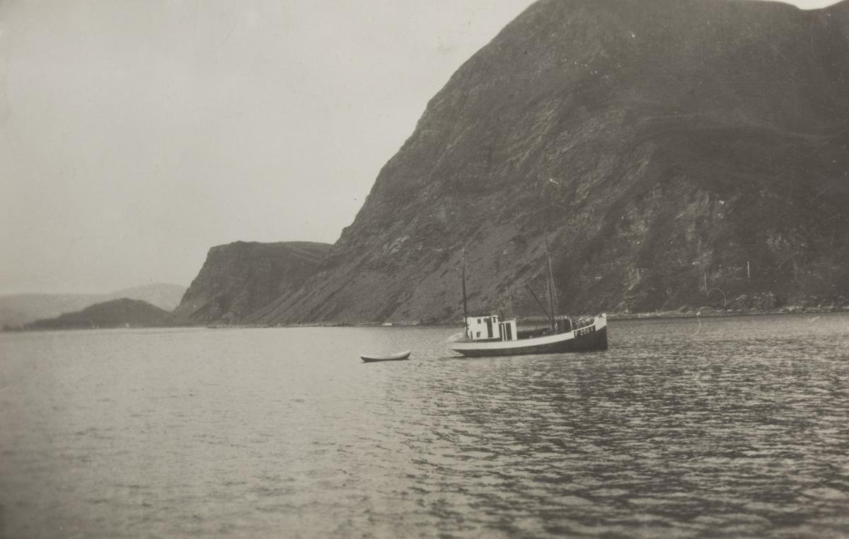 """M/K """"Høvring"""", fotografert med fjell i bakgrunnen."""