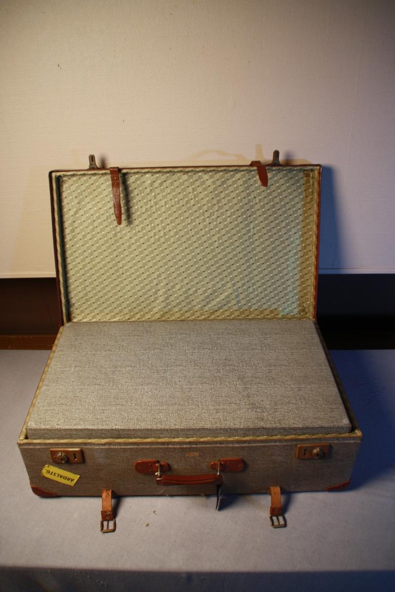 Koffert i vulkan fiber. Forsterka hjørner i skinn, handtak og to låser. To stropper i skinn over opninga til kofferten. To trestykker går over kofferten på begge sider. Sett saman med naglar. Trekt med mønstrete papir inni. Festestroppar. To oppbevaringsrom i kofferten. Adresselapp.
