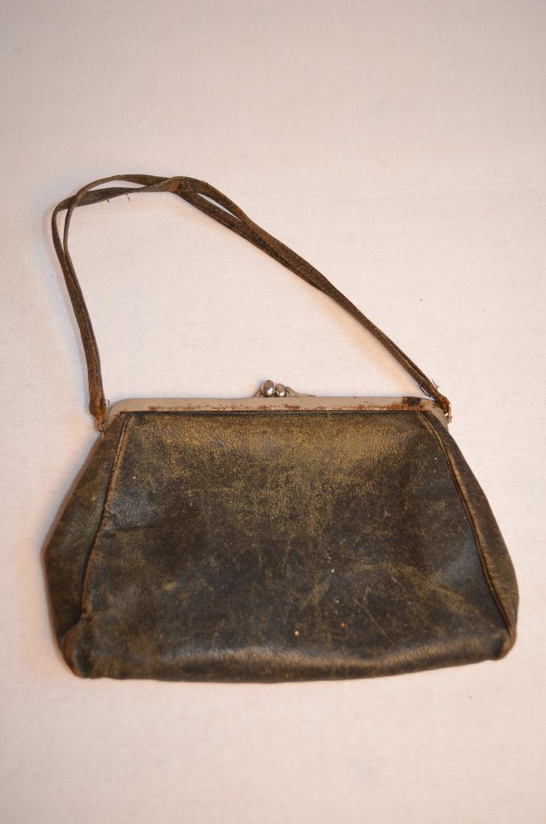 Slitt skinnveveske med bærehank av to skinnreimer og lås i stål. Ei mindre lomme med knapp på framsida. Inni er veska trekt med rosa stoff og har ei lita lomme.