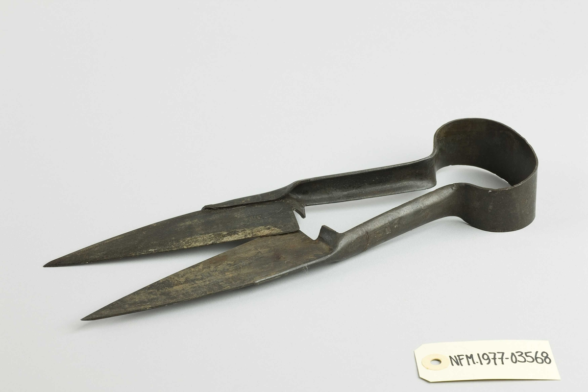 Saks. Er laga av eitt stykke metall. Er rund nedst på skaftet. Øvst, to like store og kvasse blad.