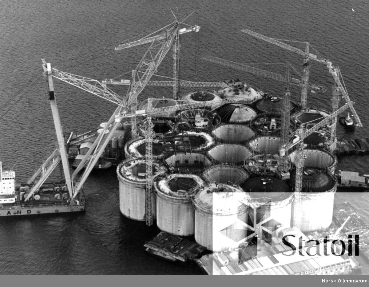 Betongunderstellet til Statfjord B er under bygging i Gandsfjorden ved Stavanger i oktober 1979 . Etter at installasjonsarbeidene i cellene stort sett er ferdig, lukkes disse med en betongkappe og plattformen klargjøres for støping av betongskaftene.