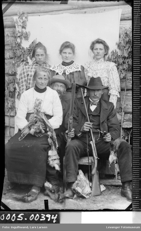 Gruppebilde av fire kvinner og to menn med geværer og trofeer fra jakta.