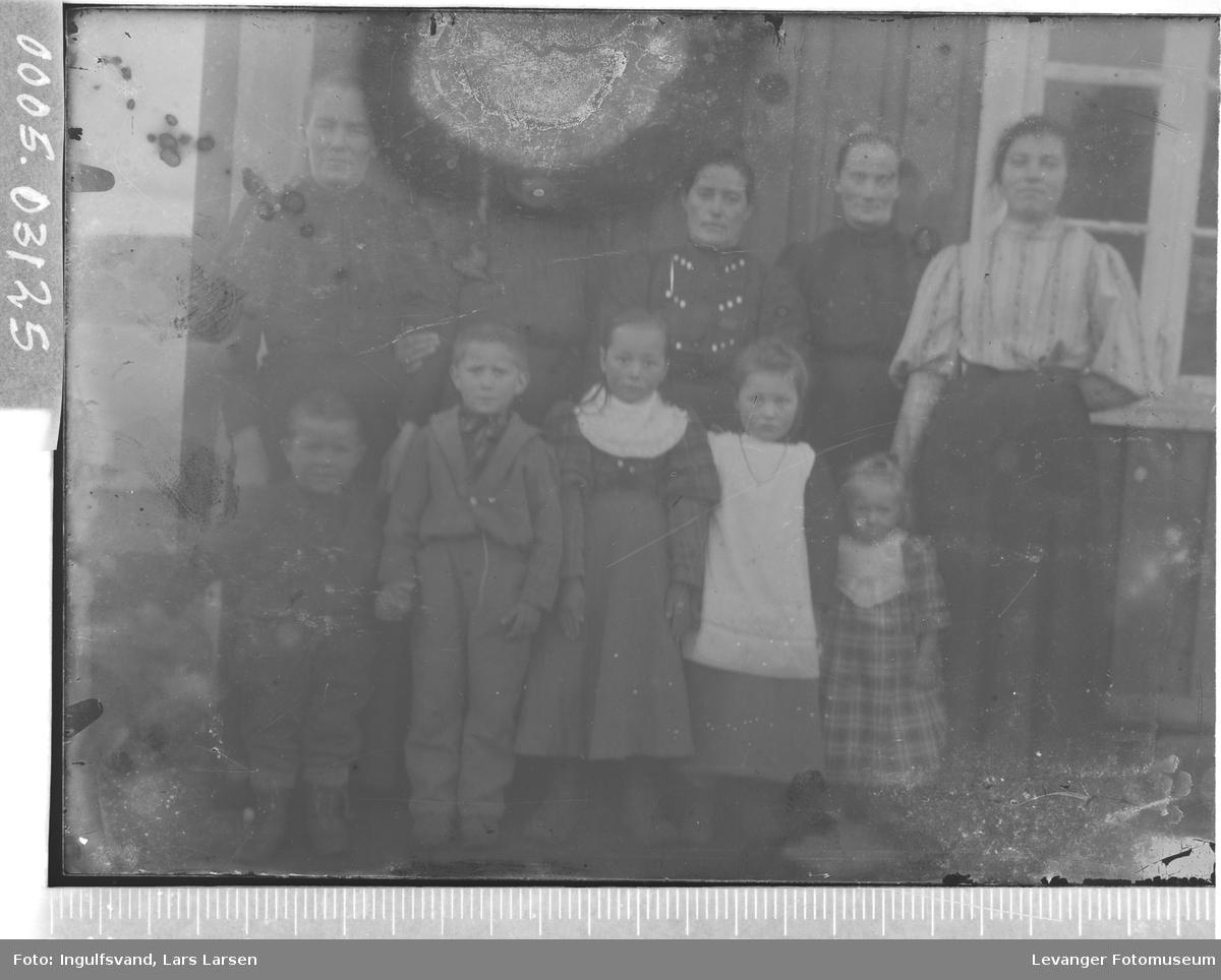 Gruppebilde av fem kvinner og fem barn foran en bygning.