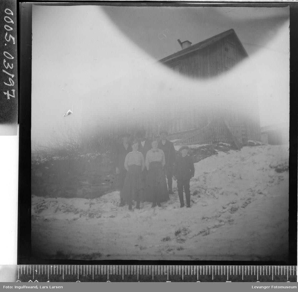 Gruppebilde av tre menn, to kvinner og en gutt foran en bygning.