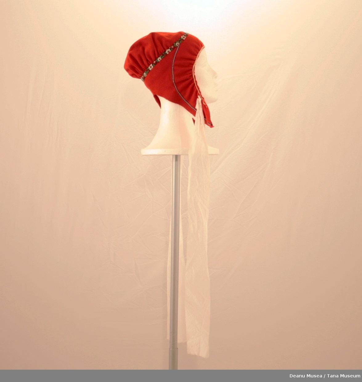 Rød samisk jentelue. Blå pyntebånd med hvite ogrøde blomster. Knytebånd av hvit silke.