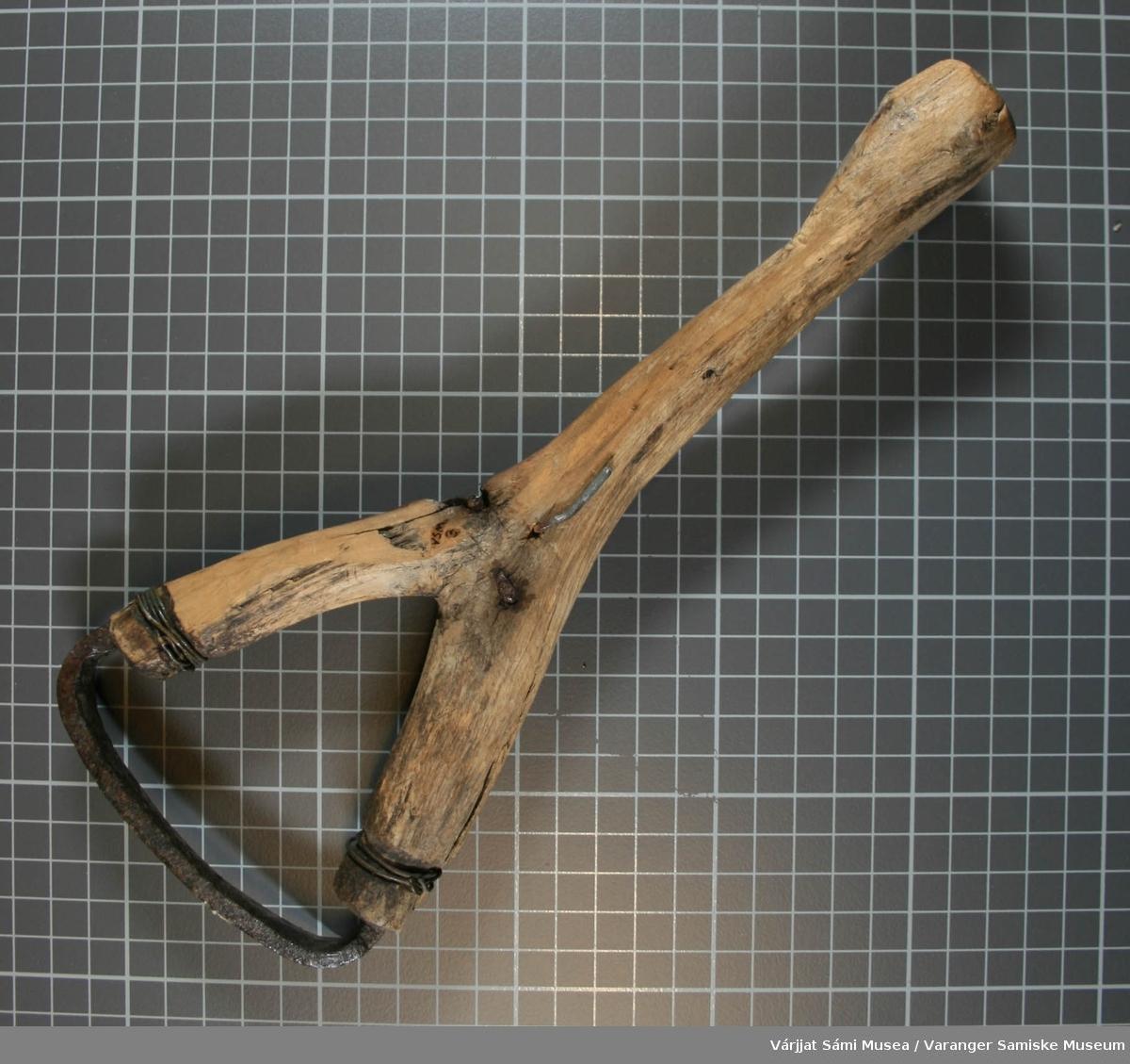 Barkskrape avr laget av tre og metall. Y-formet skaft og svakt buet blad.  Det er laget spor i treet for selve skrapen, i tillegg er den festet med streng og slått gjennom treet.