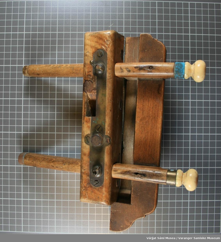 """En høvel av tre (eik/bøk) med blad av jern. Den har 2 deler.  Ene delen er tredd inn på 2 """"armer"""" av tre som er festet oppå den andre delen. På hver av armene er det en knott som er av bein el. bakkelitt. Bladet mangler. Delen uten armer er veldig tung, fordi den har en kant av messing/kobber som går langs hele langsiden (under) Det ser ut som om høvelen er fabrikklaget. Den er meget forseggjort."""