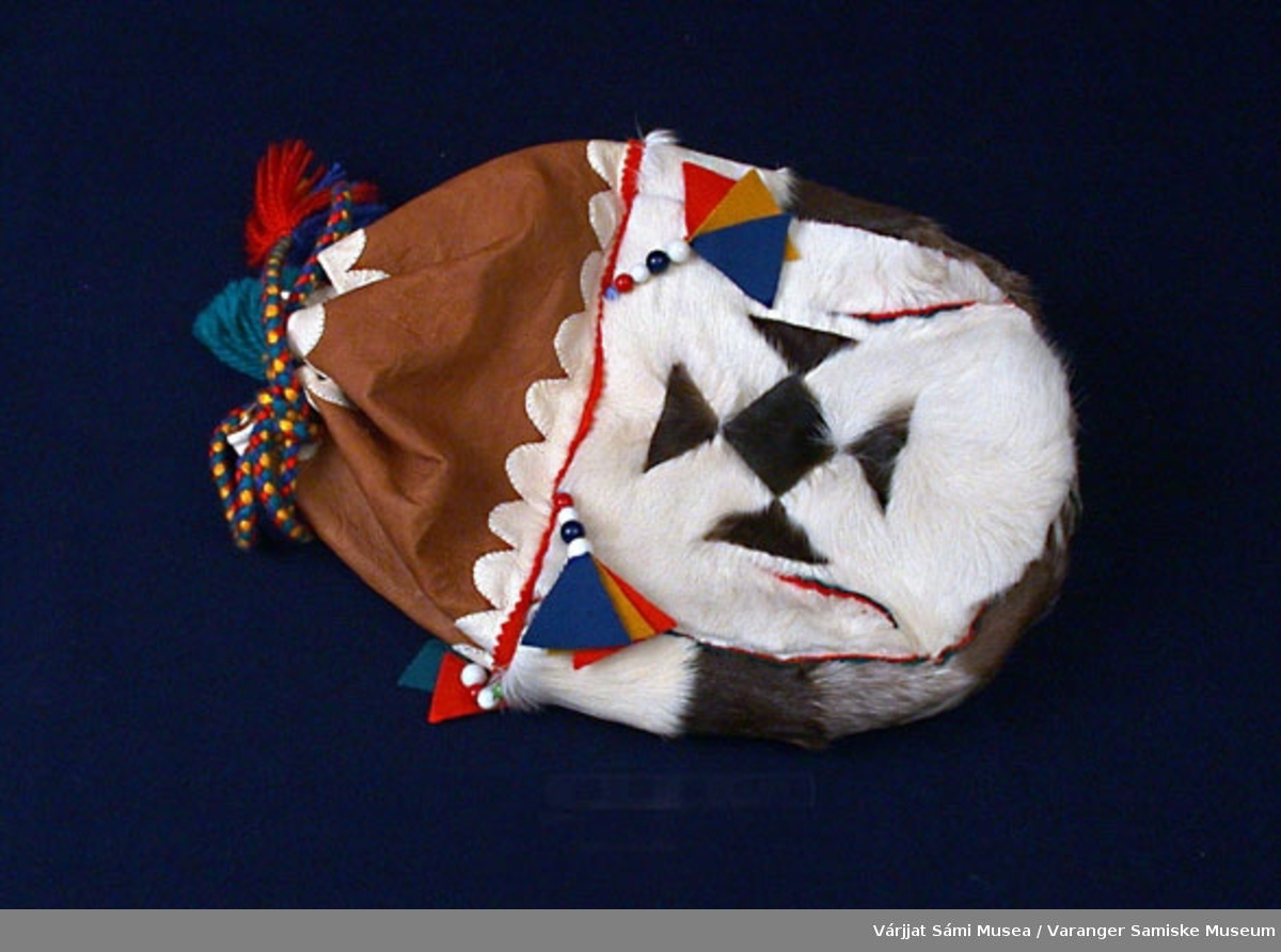 Sekken er sydd av sisti (reinskinn). Pyntet med klede og perler.