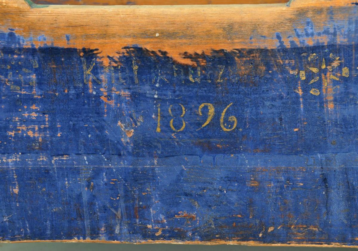 Vogge sett saman av fire åttkanta, svartmåla hjørnestolpar med ei dreia kule i toppen av kvar. Vangar og endestykke er måla i blått. Namn og åtstal er måla med gul skrift på eine vangen. To lause fjølar i botn som er måla i raudt på eine sida.