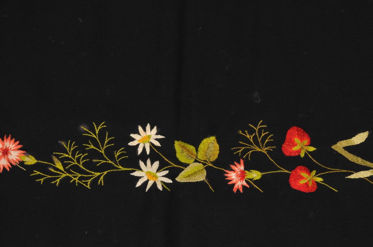 Forkle i svart ullrips med broderi nederst og litt opp langs eine sida. Motiv på broderiet er naturalistiske blomar, sauma med silketråd og i sjattersaum.