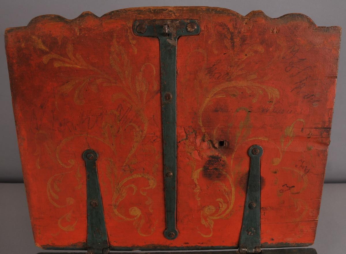 Skrin med hengsla pultlok og ein skuff. Skuffen har seks små rom. Skrinet har profilera utskjeringar i fronten. Det er måla i ein mørk blågrøn farge med ein raud kant rundt loket og rosemåling i raudt.