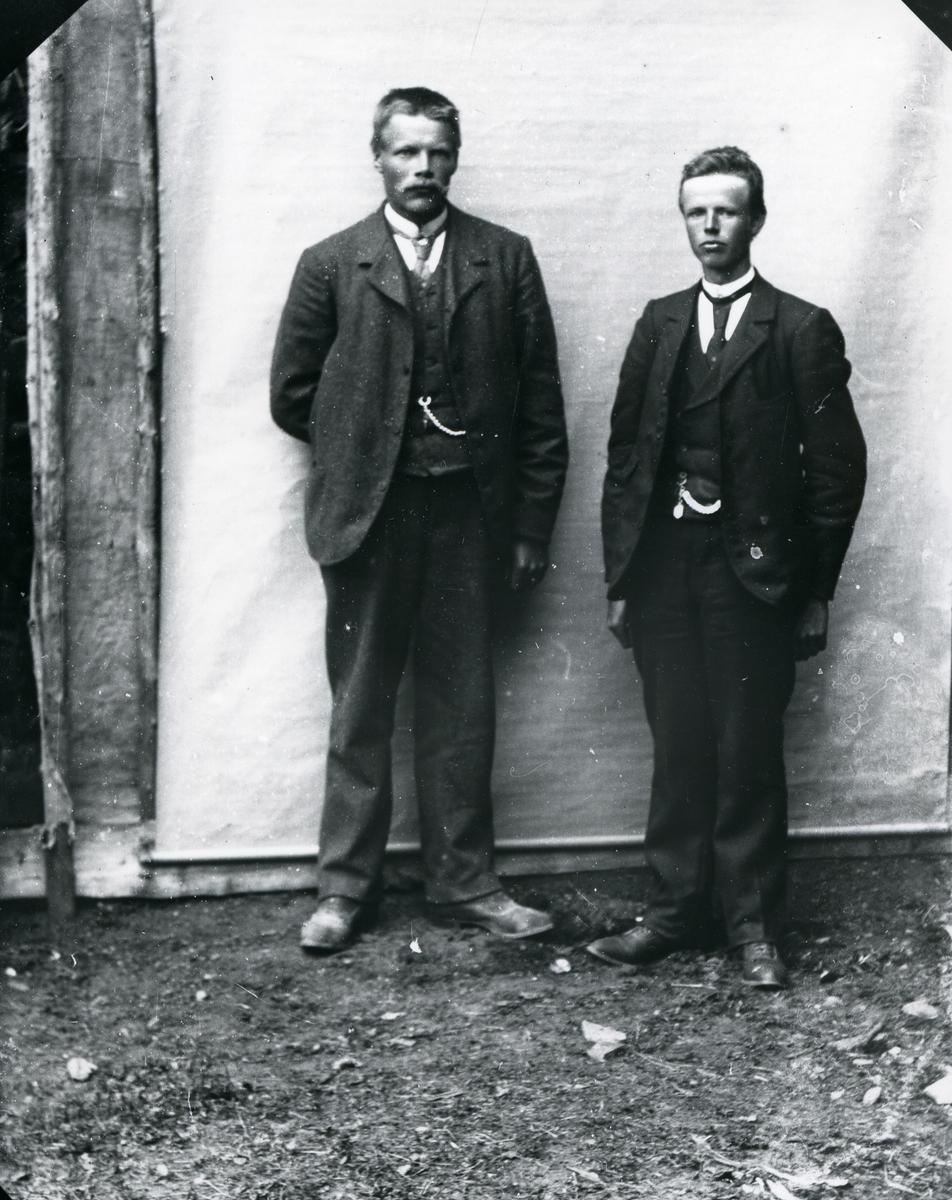 To dresskledde menn, stående foran lerret