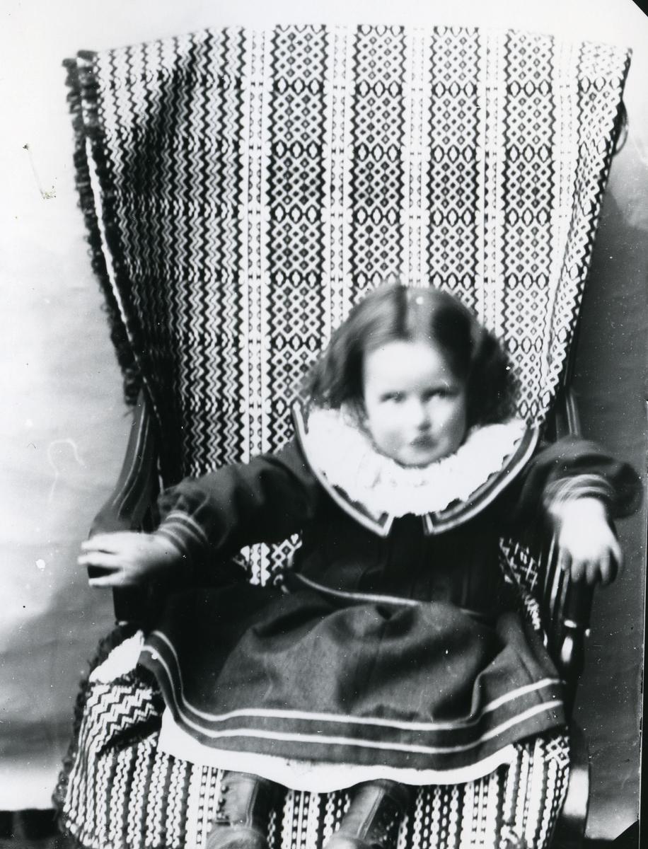 Jente i mørk kjole sittende i gyngestol med mønstret pledd