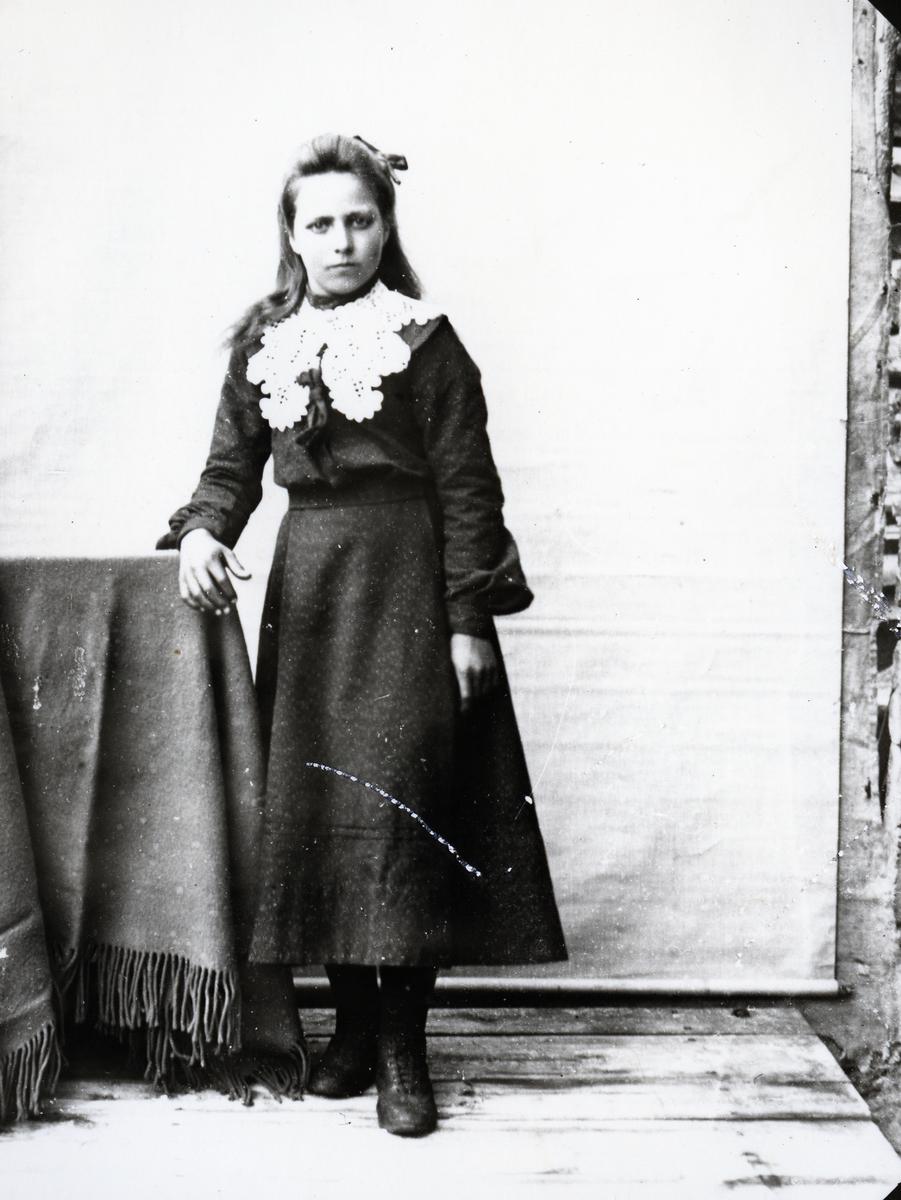 Ung kvinne i helfigur, stående ved tildekket stol foran lerret