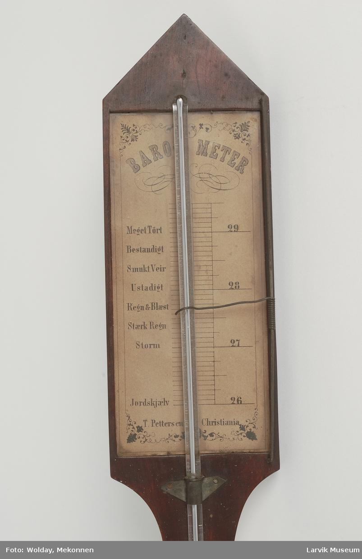 Form: rekt.topparti som ender i en spiss, utbuet midtparti, nederst rektangulært deksel. innstillbar viser til høyre Kvikksølvbarometer.