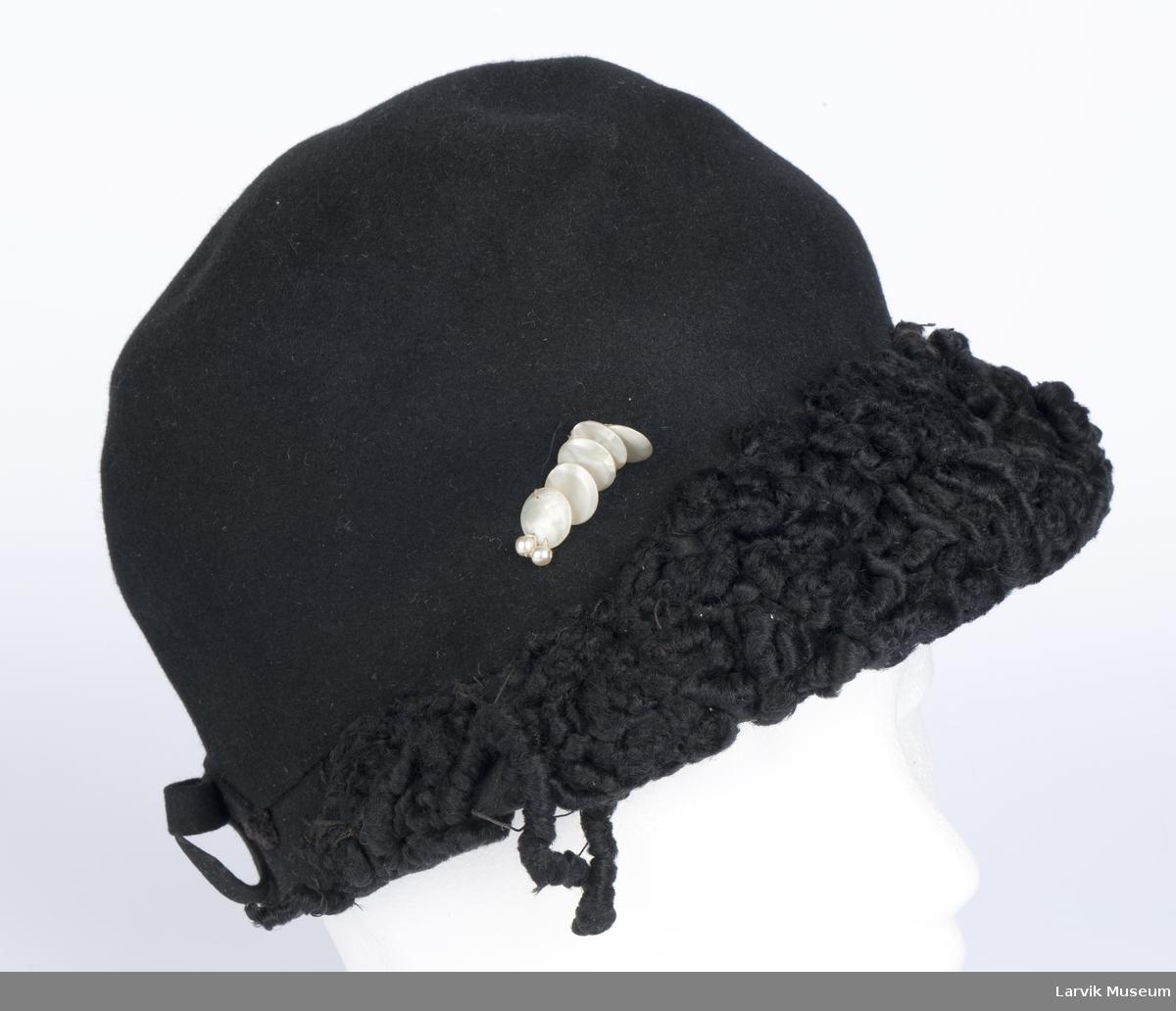 Form: sort filt, langs forsiden besetning av sort persianerimitasjon og garnityr av 5 plater perle- morsimitasjon og 2 små perler, filtsløyfe bak, sort ripsbånd på innsiden, omsydd