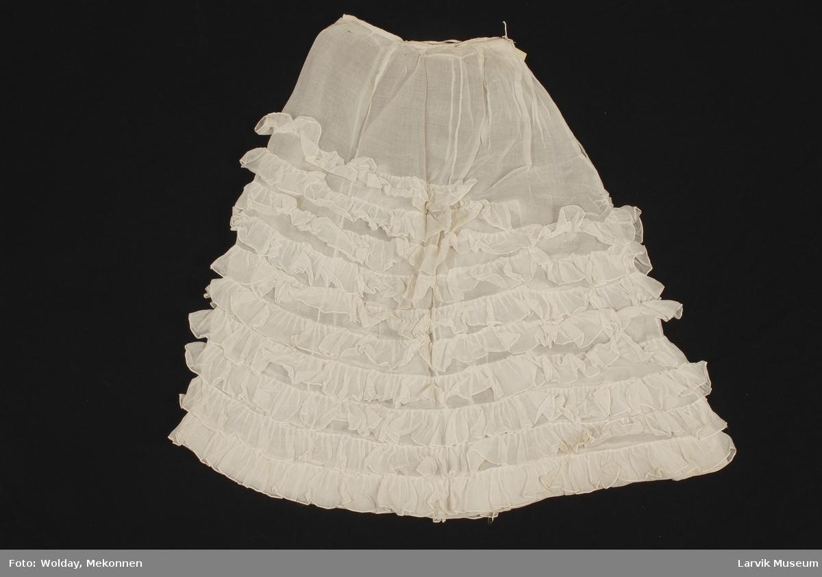 Form: Tynn gjennomsiktig bomull. 8 rader med ryskjekanter påsydd i samme stoff fra kneet og ned. 2 rysjekanter over kneet i forkant.  Hemper i linning for lukking.
