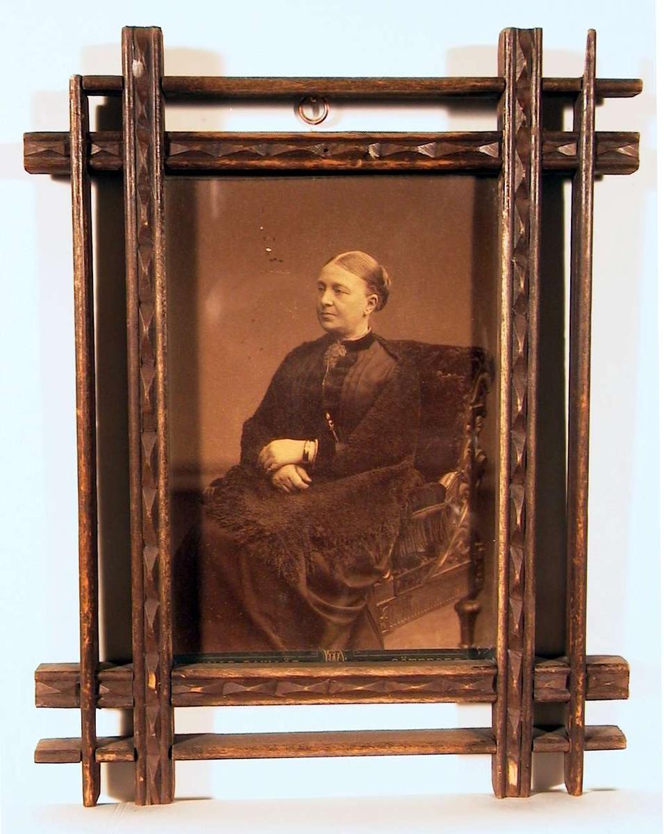Portrett av eldre dame i sort med sort sjal sittende i stor lenestol i kvartprofil.