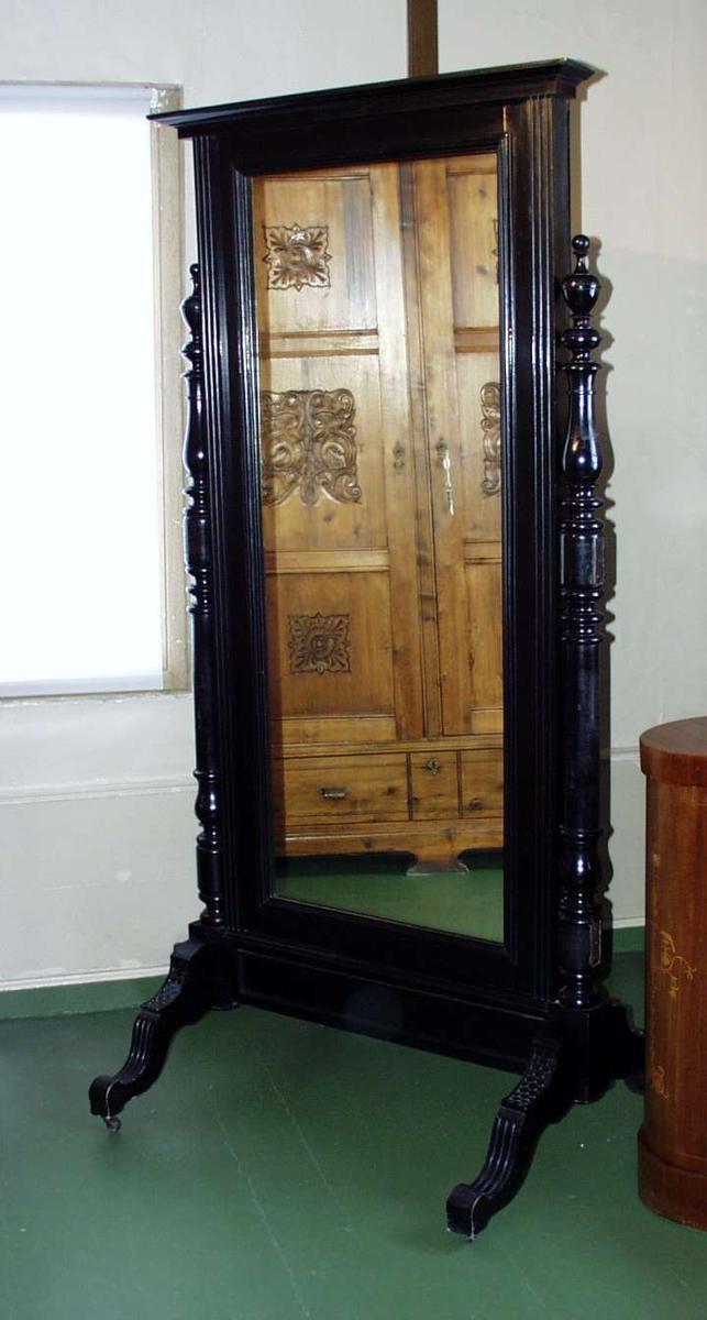 Svart malt speil i tre. Speilrammen har paralelle striper og rikt utskårede bærestolper som ender i utsvungne ben. Benene har små hjul.