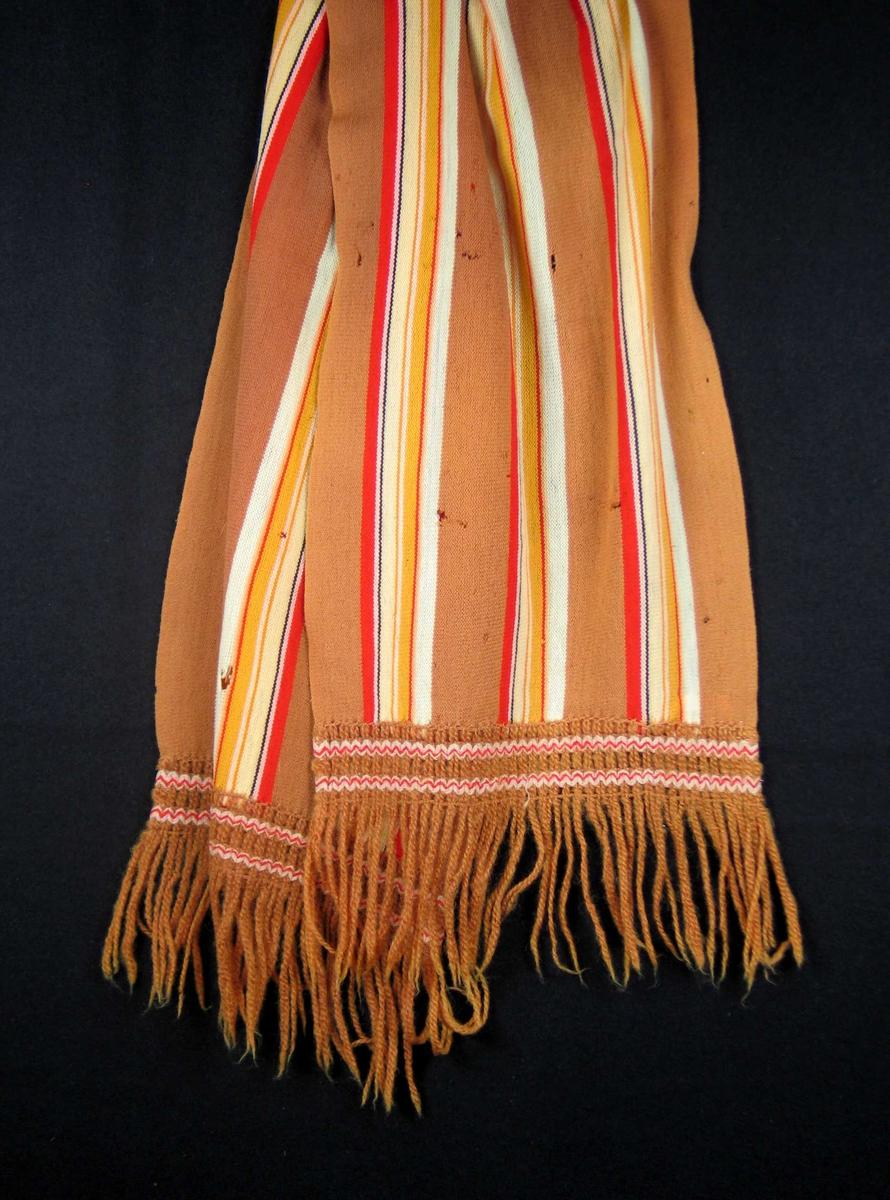Stripet maskinstrikket skjerf strikket av veldig tynn og myk ull. Bunnfargen er lys brun med tre like striperapporter jevnt fordelt på langs. Frynser.