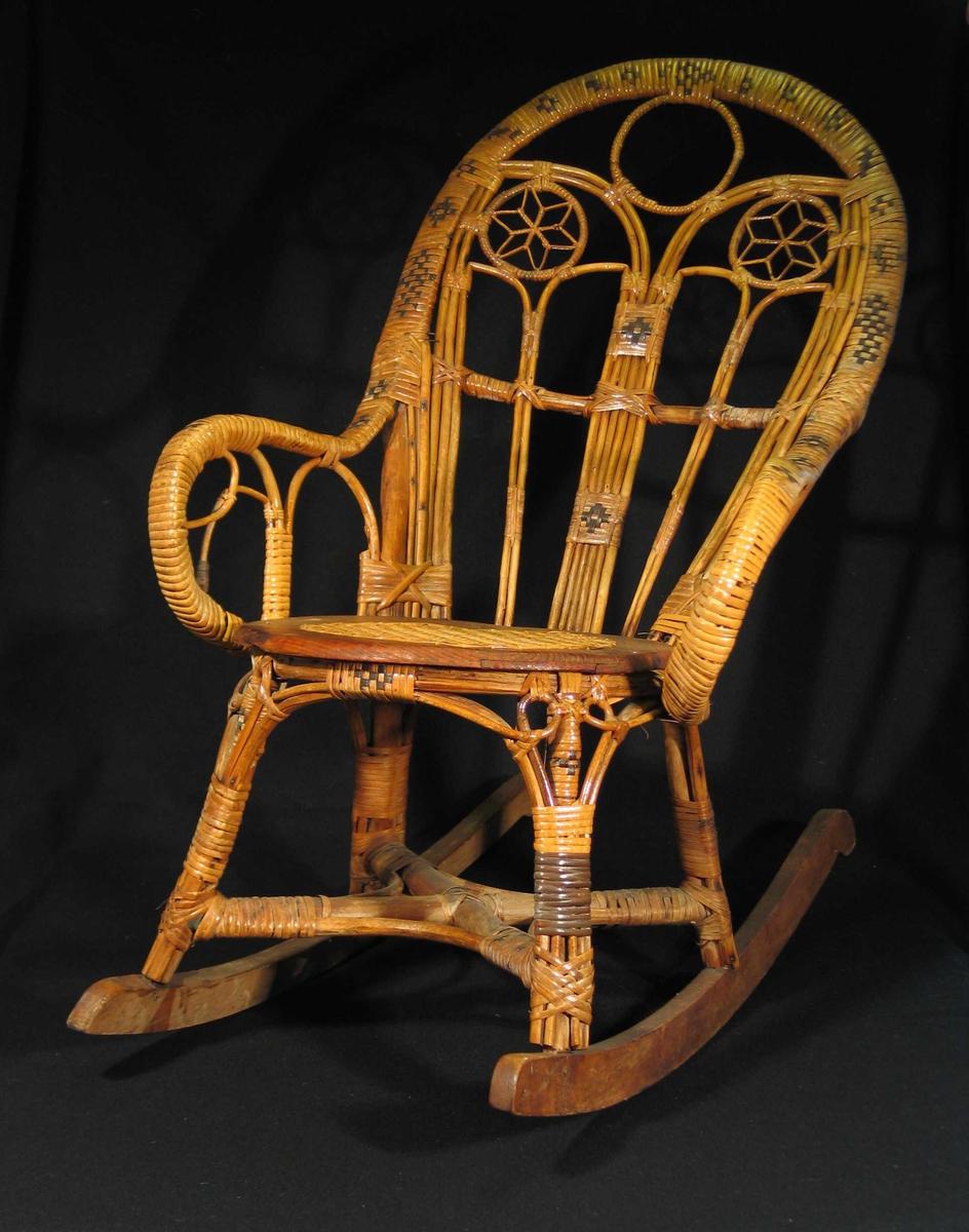 Flettet kurvstol med armlener og høy rygg. Setet er en trering med rottingfelt i midten. Mønster i rygg og på armlener der mørkere felt er flettet inn. Stjernemønster i ryggfeltet.