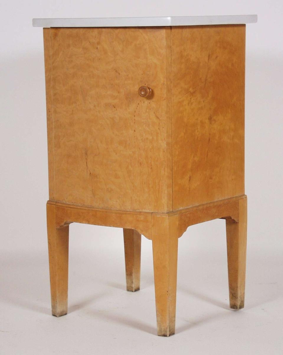 Nattbordet er i lakkert flammebjørk med eik innvendig. En skapdør skjuler en skuff. Øverst er en marmorplate som på undersiden har tekst.