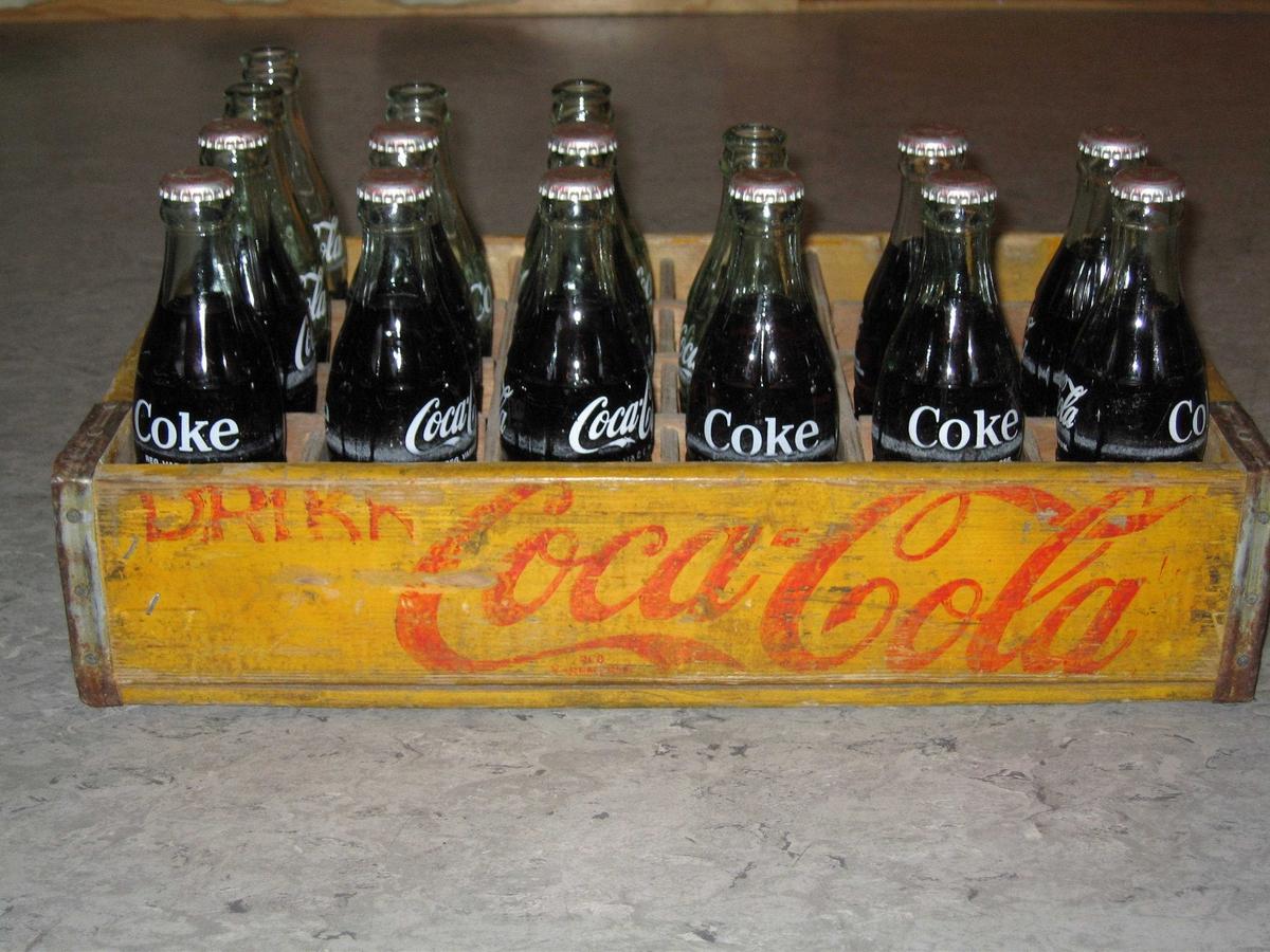 Trekasse til små colaflasker. Kassen inneholder 11 flasker med innhold og 5 uten.