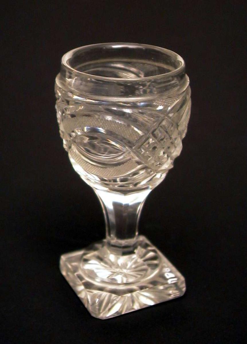 Støpt, tykt vinglass med firkantet fot. Det er gått skår av foten.