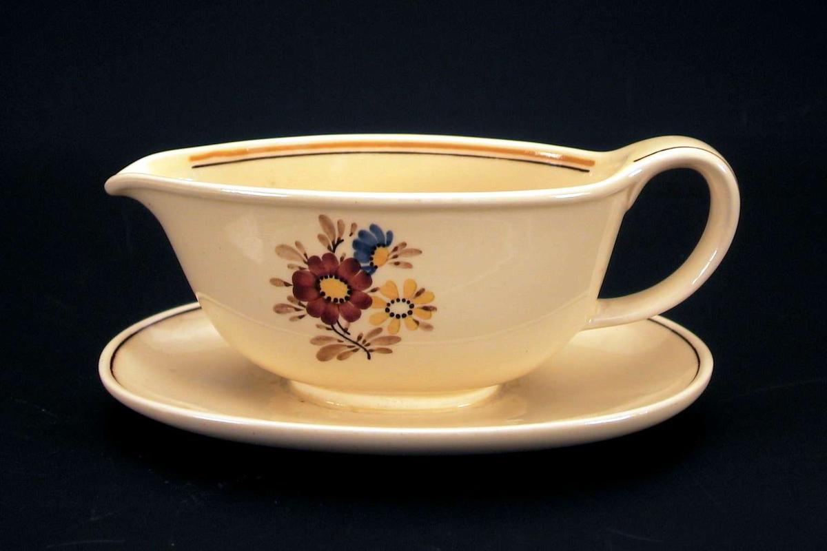 Sausenebb i gul keramikk med blomsterdekor, langs kanten en oker og en brun linje.