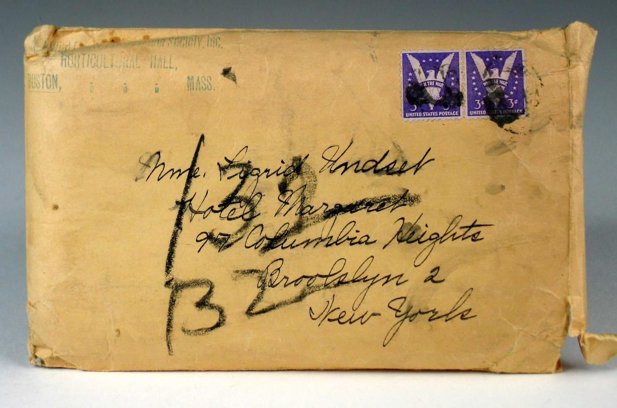 Brun konvolutt med to frimerker. Motivet på frimerket er en fredsdue med teksten: Win the war.